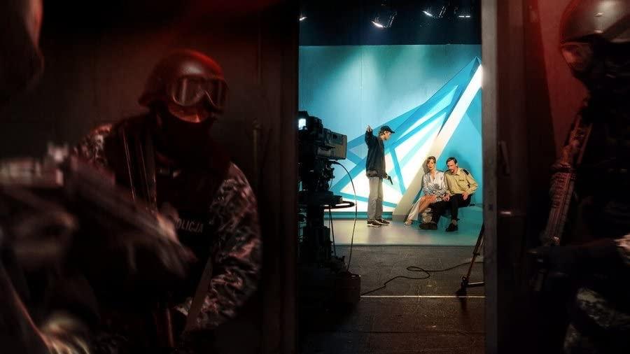 Cena do filme Interrompemos a Programação. Sebastian, Mira e Grzegorz estão, nessa ordem, ao fundo da imagem em um set de filmagem, vistos de uma porta entreaberta. Sebastian - homem branco, loiro, de calça bege, boné e jaqueta preta- está em pé empunhando uma arma, e os outros - Mira, uma mulher branca, ruiva, de vestido prateado, e Grzegorz, homem branco, moreno, com uniforme de guarda - estão sentados e algemados. Do lado de fora, 2 policiais equipados com armas na mão.