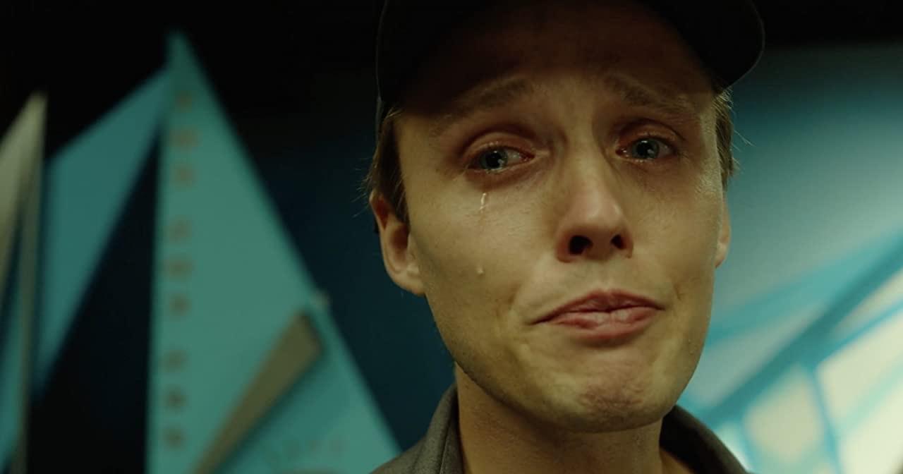 Cena do filme Interrompemos a Programação. A imagem foca o rosto do personagem Sebastian, um homem branco, loiro e olhos azuis. Na cena, o homem usa um boné preto e está chorando.