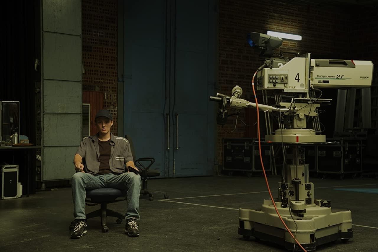 Imagem do filme Interrompemos a programação. Na imagem o protagonista Sebastian - um homem branco, de boné preto, calça jeans, camiseta marrom e camisa cinza - está sentado em uma cadeira no canto esquerdo, ao lado direito há uma grande câmera de filmagem. O cenário do fundo é escuro em um estúdio de televisão.