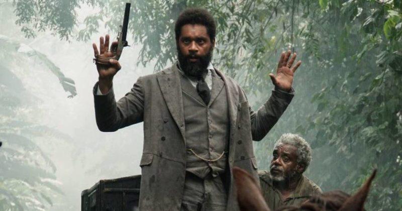 Cena do filme Doutor Gama. Na imagem encontra-se o personagem Luiz Gama, um homem negro, barbudo, trajado com um terno acizentado, calça no mesmo tom e uma gravata mais escura. Ele está com as mãos levantadas, como sinal de rendição, e em uma delas segura uma arma. Ele está em pé. Abaixo dele, sentado na charrete preta, está o escravo Santos. Ele veste uma blusa surrada em tom escuro, é um homem negro de mais idade, possuindo cabelo e barba brancas.