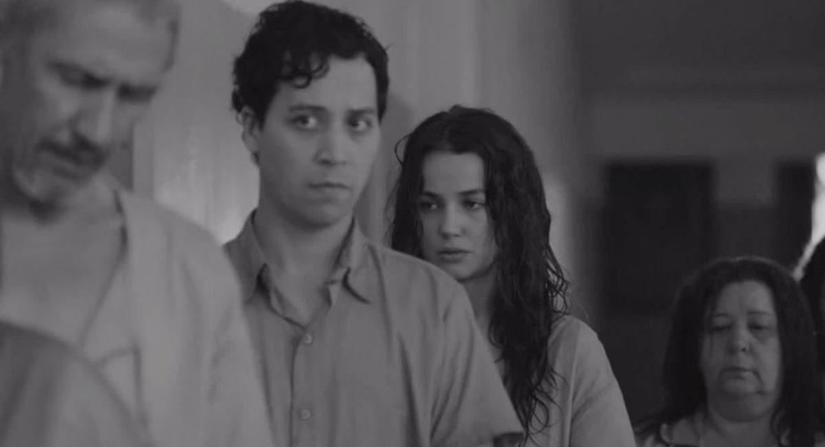 Cena da série Colônia. Na imagem aparecem os personagens Gilberto e Eliza centralizados entre outras duas figuras que estão desfocadas nos cantos. Todos usam a camisola cinza do hospício e tem aparência cansada, a imagem está em preto e branco.