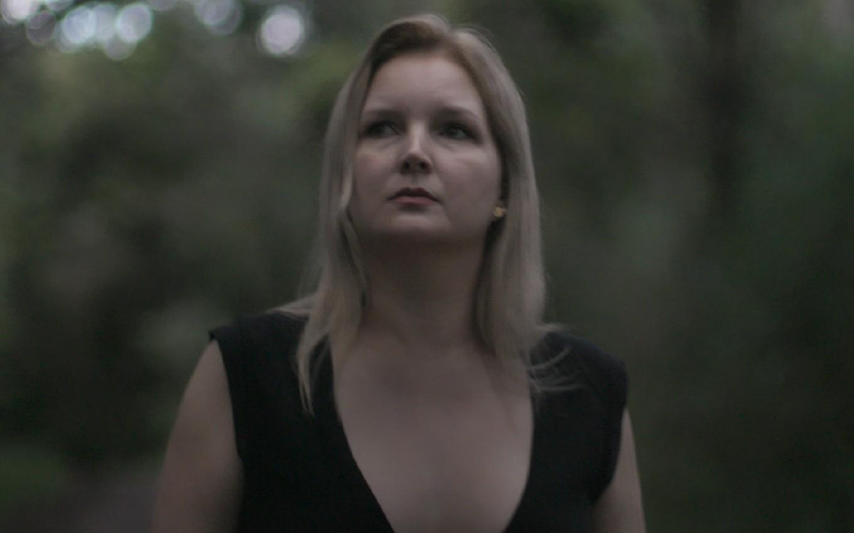 Cena da série documental Elize Matsunaga: Era uma vez um crime. Na imagem encontra-se Elize, uma mulher branca de cabelos lisos e loiros, ela está com o olhar de lado e com uma expressão ríspida. Usa um vestido preto decotado e de mangas curtas. Ao fundo está uma floresta desfocada.