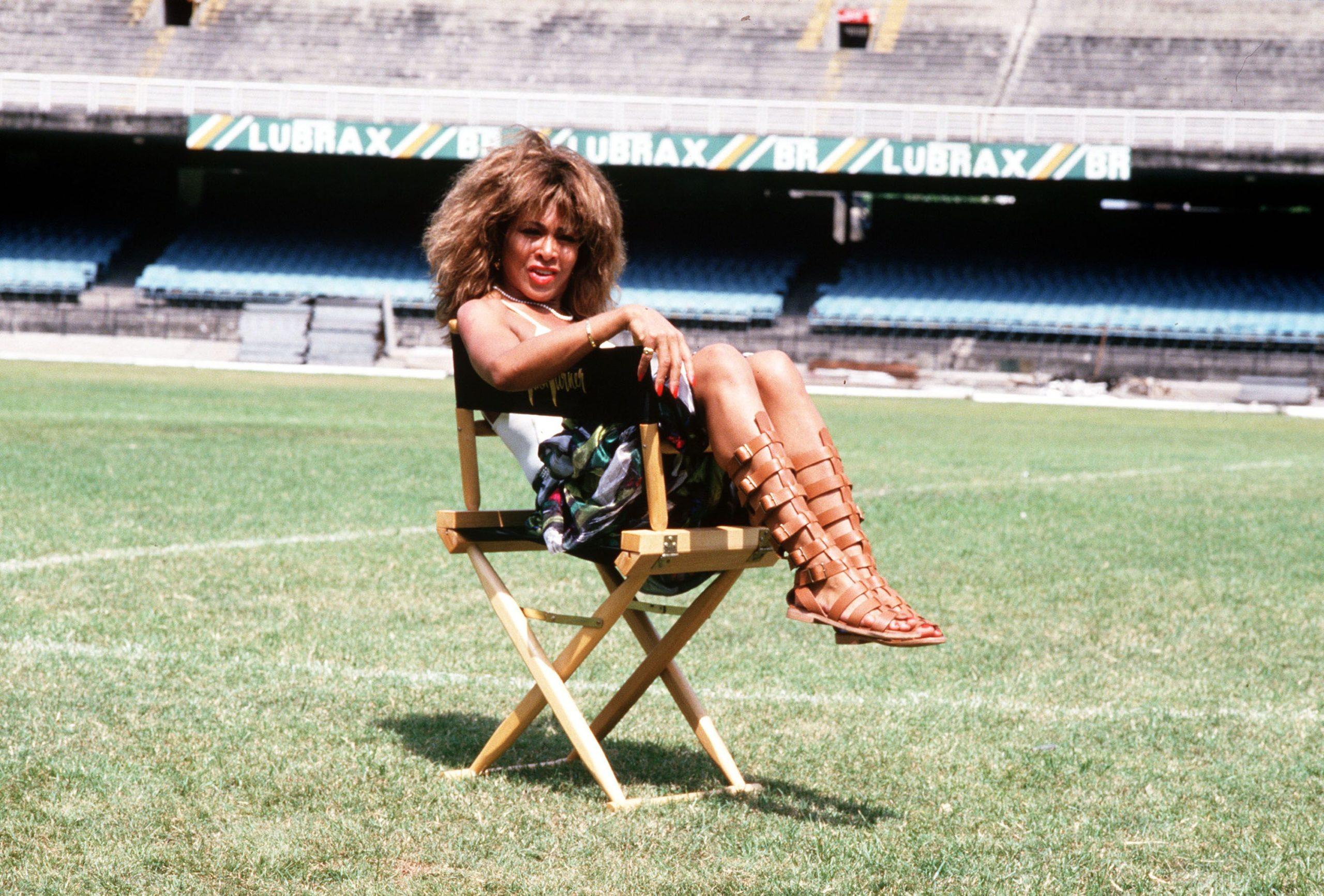 Fotografia retangular da cantora Tina Turner. Ao fundo, vemos um estádio de futebol. No centro, sentada em uma cadeira, a artista se dispõe de lado, com pernas dobradas e boca levemente aberta. Ela é uma mulher negra, com sandálias gladiadoras, esmalte e batom vermelhos, um anel e outros adereços.
