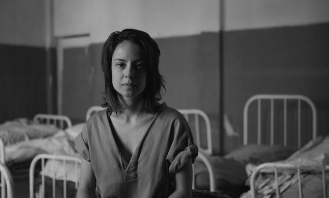 Cena da série Colônia. Na fotografia a personagem Valeska está sentada em uma das camas do hospício, a personagem veste a camisola cinza e a imagem é em preto e branco.