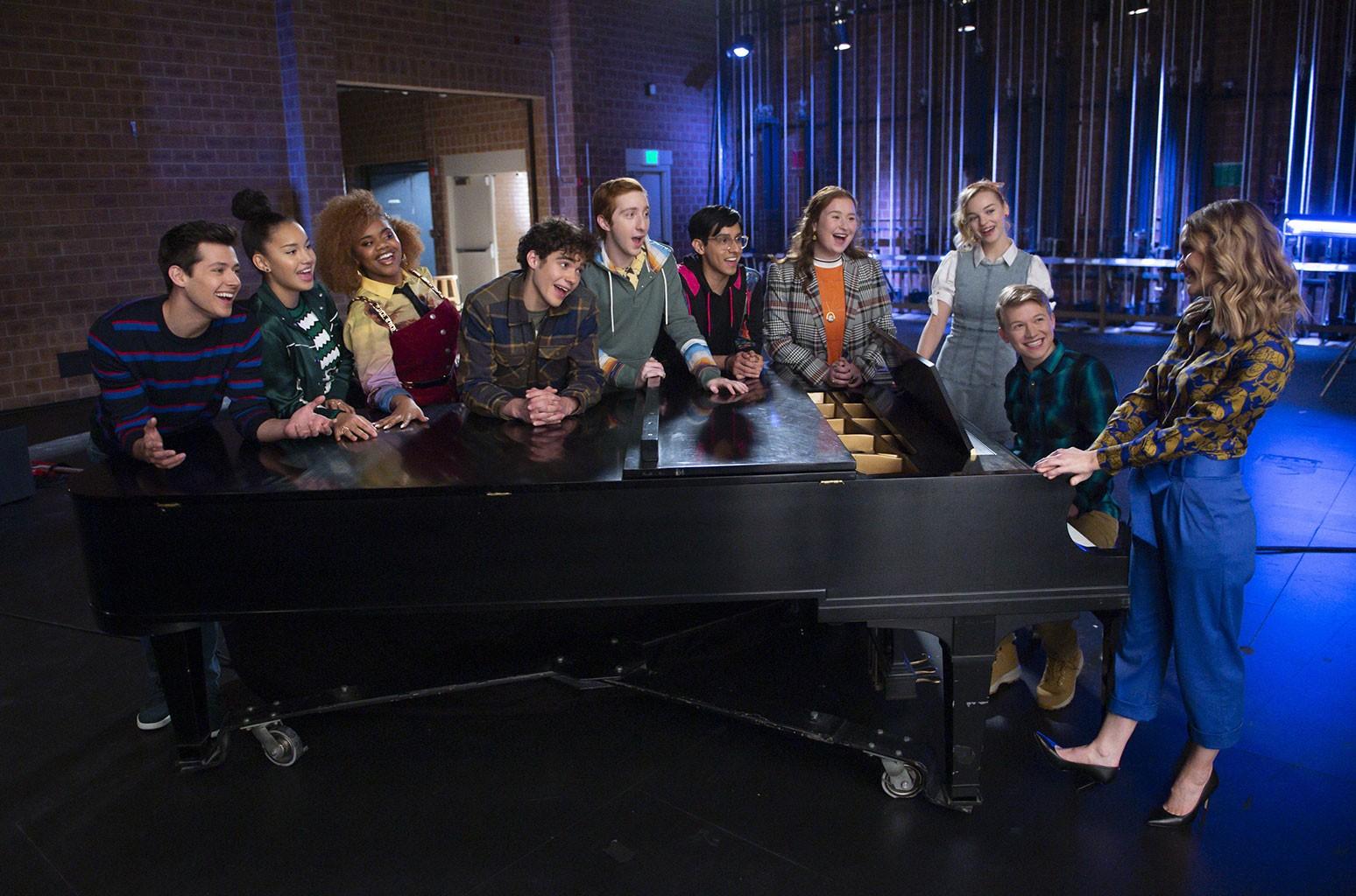 Imagem da série High School Musical: The Musical: The Series. Na imagem, podemos ver, apoiados sobre um piano preto, da esquerda para direita, um homem branco de cabelos pretos usado uma blusa listrada azul e preta; uma mulher negra, de cabelos pretos, usando uma blusa listrada preta e branca e uma jaqueta verde; uma mulher negra, de cabelos castanhos, usando uma camisa amarela e uma jardineira vinho por cima; um homem branco, de cabelos pretos, usando uma camisa verde, azul e bege; um homem branco, de cabelos ruivos, usando um moletom verde escuro; um homem negro, de cabelos pretos, usando uma blusa preta e vermelha; uma mulher branca, de cabelos ruivos, usando uma blusa laranja com uma jaqueta quadriculada cinza por cima; uma mulher branca, loira, usando um vestido cinza, sob uma camiseta branca; um homem branco, loiro, usando uma camisa xadrez verde, sentando de frente ao piano, tocando ele; e por fim, uma mulher branca, de cabelos loiros, usando uma camisa bege e azul e calças azul, saltos finos pretos, no canto direito da imagem. O fundo é uma cortina de teatro azul e um espelho que a reflete.