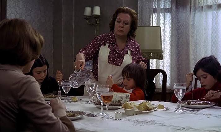 Cena do filme Cría Cuervos em que a família está sentada à mesa se alimentando. A tia Paulina, que é uma mulher branca, de cabelos castanhos claros e curtos, aparece usando uma camisa rosa claro, sentada de costas para a imagem. Irene, a irmã mais velha, que é branca, de cabelos castanhos, lisos, na altura dos ombros, aparece comendo no fundo da foto. Rosa, uma mulher branca de cabelos castanhos claros e curtos, que usa um vestido rosa florido e um avental branco, serve água à Maite, a irmã mais nova, que é branca de cabelos castanhos e curtos. No canto bem a direita está Ana, branca, de cabelos castanhos, lisos e curtos. No centro está a mesa, repleta de taças e pratos com comida e no fundo há um abajur, uma cortina e uma lâmpada fixada na parede.