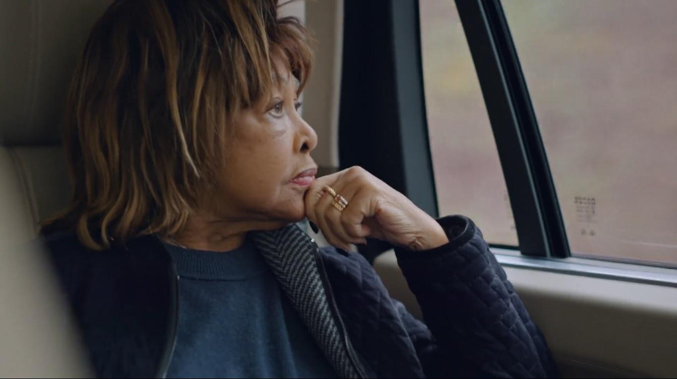 Cena do documentário Tina. Na imagem, vemos a cantora Tina Turner dentro de um carro, disposta de perfil, olhando pela janela e apoiando o rosto em sua mão fechada. Ela é uma mulher negra, de cabelos loiros, com semblante reflexivo e veste roupas de frio.