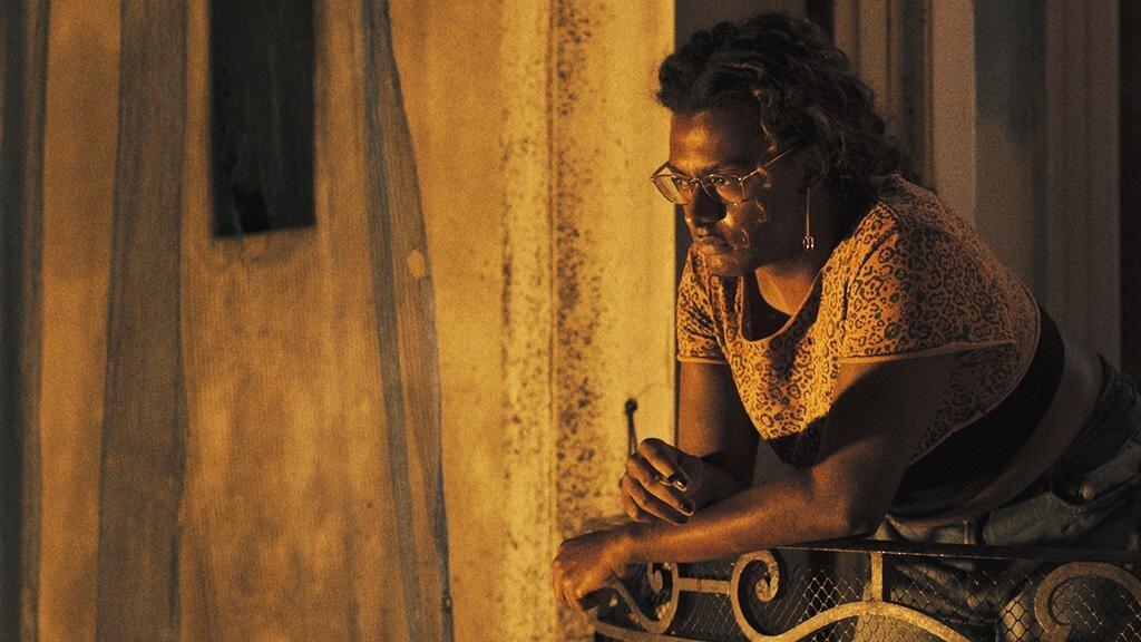 """Cena da série """"Manhãs de Setembro"""". Na imagem, a personagem Cassandra usando roupas estampadas e apoiada na varanda. A imagem possui tons dourados. A personagem está situada à direita da foto, olhando para o horizonte."""