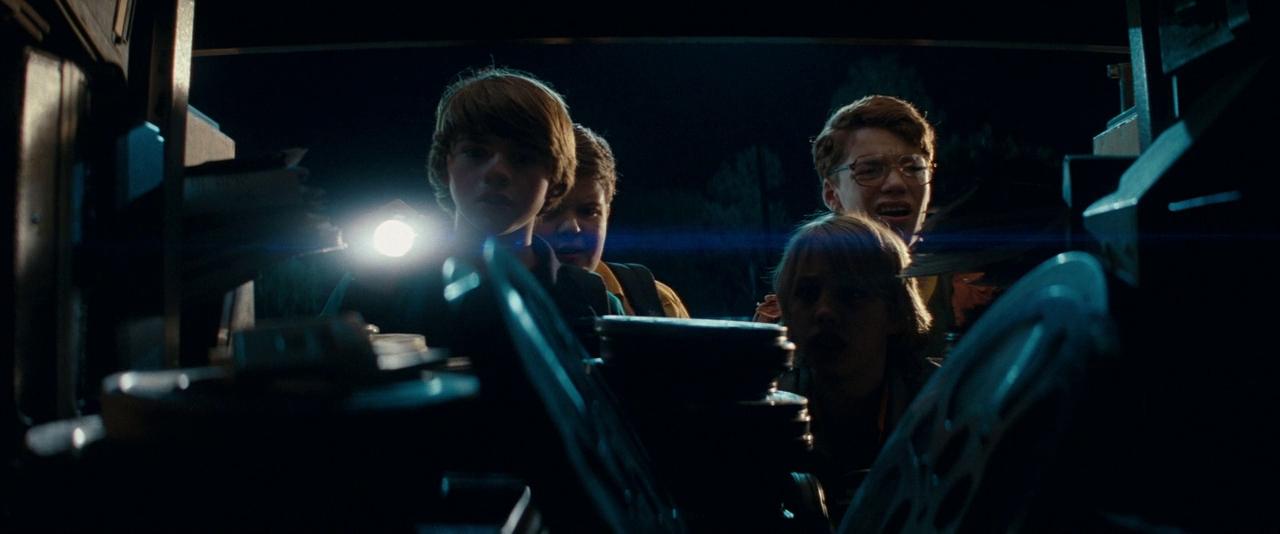 Fotografia do filme Super 8. É uma foto escura. Em primeiro plano há vários rolos de filmes iluminados fracamente por uma lanterna, que é a única fonte de luz da imagem. Em segundo plano, de frente para os rolos de filme e para a câmera estão quatro garotos. O que que se encontra mais à esquerda e segura a lanterna é Joe, personagem de Joel Courtney, um garoto branco de cabelos castanhos e lisos. Ao seu lado está Cary, o personagem de Ryan Lee, um garoto branco, baixo, de cabelos loiros que vão até os ombros. Ele é o que menos está sendo iluminado pela lanterna. Atrás dele está Martin, interpretado por Gabriel Basso, um garoto branco, ruivo e alto que usa óculos. Ao lado de Martin está Charles, papel de Riley Griffiths. Ele é um garoto branco, de cabelos castanhos e curtos. Ele tem uma mochila nos ombros e está parcialmente escondido por Joe, que se encontra em sua frente. No fundo é possível ver o céu escuro e algumas árvores distantes.