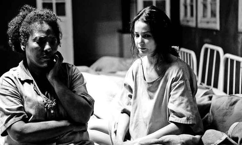 Cena da série Colônia. Na imagem aparecem as personagens Wanda e Elisa sentadas em uma cama, ambas vestem a camisola cinza da internação e a fotografia é em preto e branco.