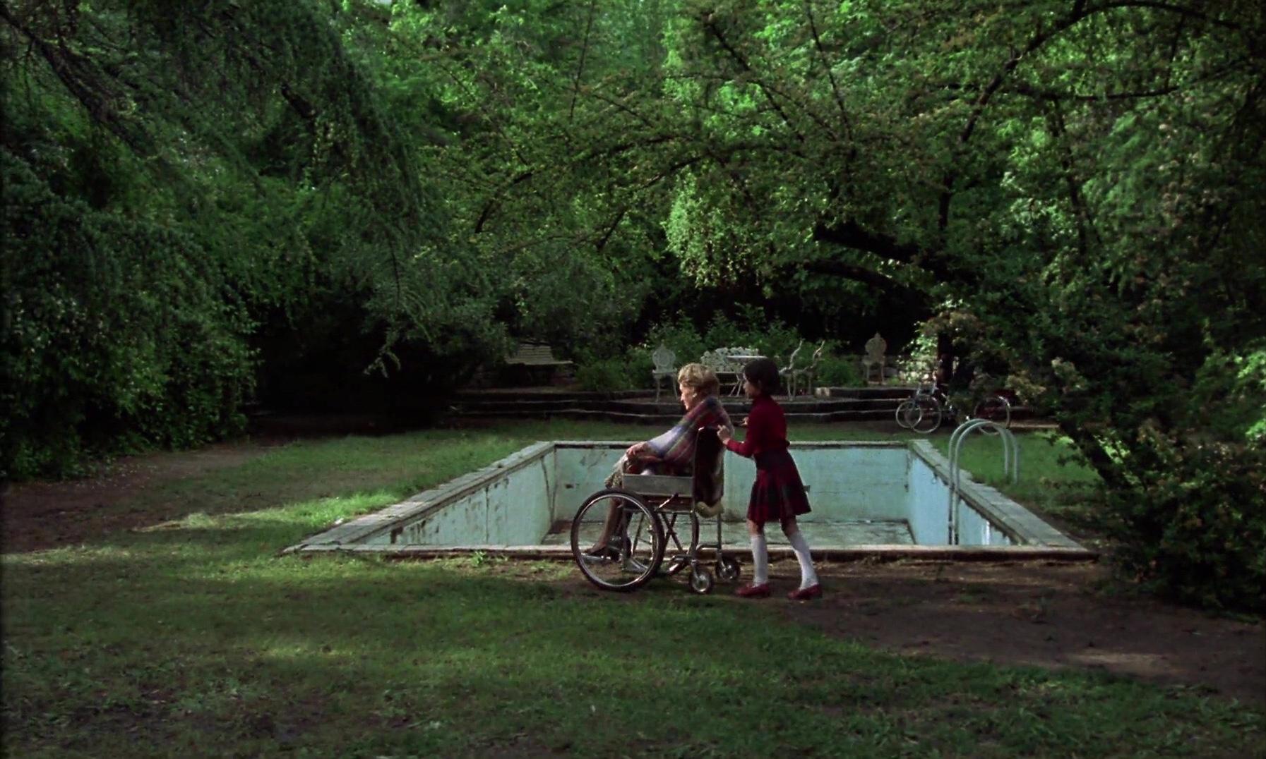 Cena do filme Cría Cuervos exibe Ana, uma criança branca, de cabelos castanhos, lisos e curtos, empurrando sua avó, uma idosa branca, de cabelos curtos grisalhos, na cadeira de rodas. Elas estão em um jardim repleto de árvores, em que há uma piscina vazia e embolorada.