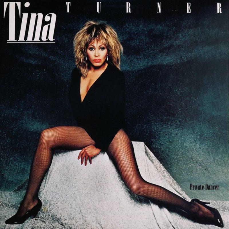 Capa do álbum Private Dancer. Fotografia quadrada, com fundo preto. No canto superior esquerdo, lemos Tina em letras brancas sublinhadas. No canto superior direito, lemos Turner em letras brancas espaçadas. Logo abaixo, a cantora Tina Turner ocupa o meio da foto de cima a baixo. Ela é uma mulher negra, sentada de pernas abertas sobre um suporte com toalha acinzentada, e veste uma blusa decotada, de manga comprida, meias-calças e saltos, todos pretos. No canto inferior direito, lemos Private Dancer em letras pretas.