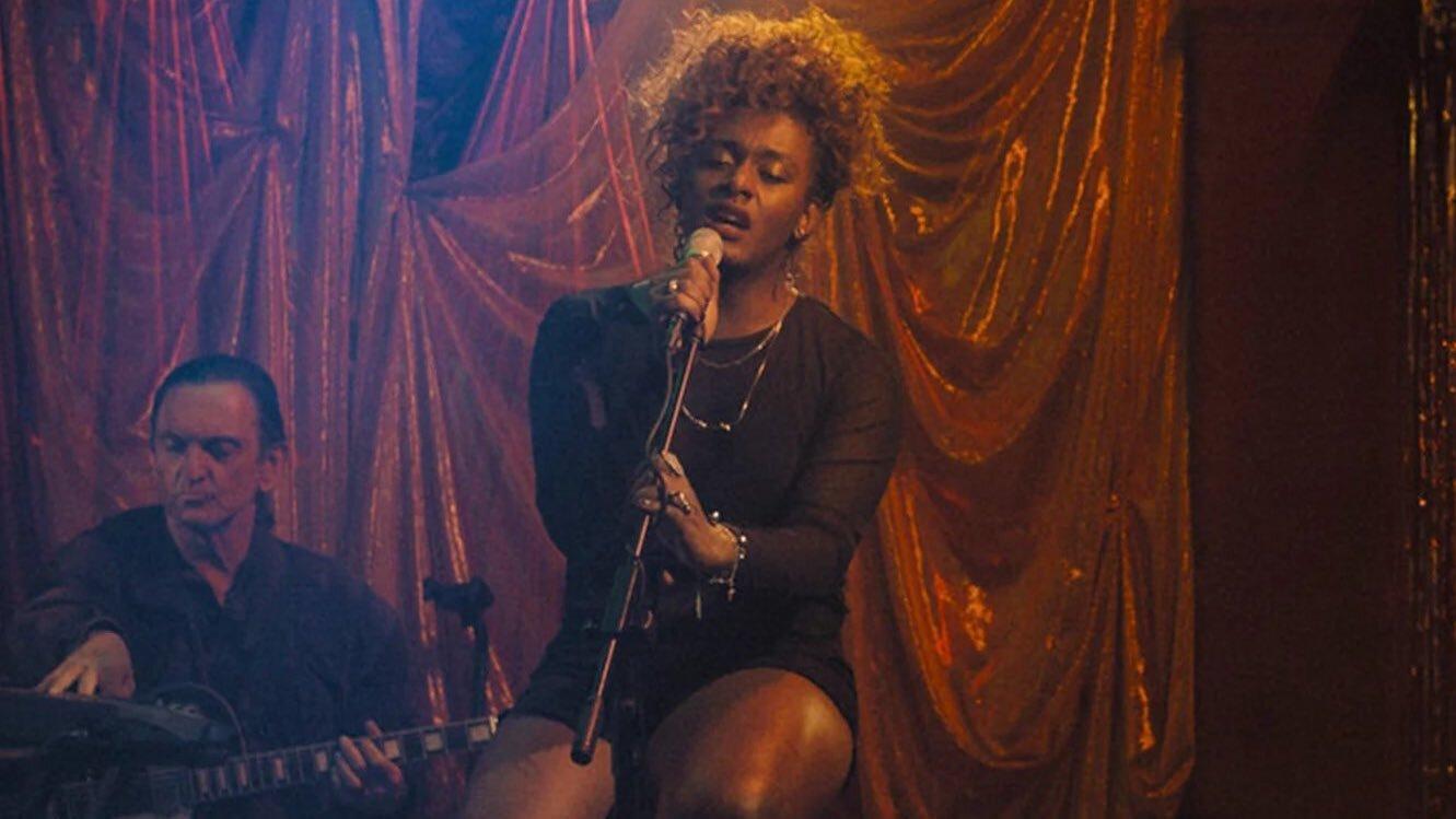 """Cena da série """"Manhãs de Setembro"""". Na imagem, a personagem Cassandra está centralizada, sentada e cantando segurando um microfone. Usa roupas pretas. Ao lado esquerdo, o personagem Décio, senhor, branco, tocando instrumentos. O fundo é uma cortina vermelha de teatro."""
