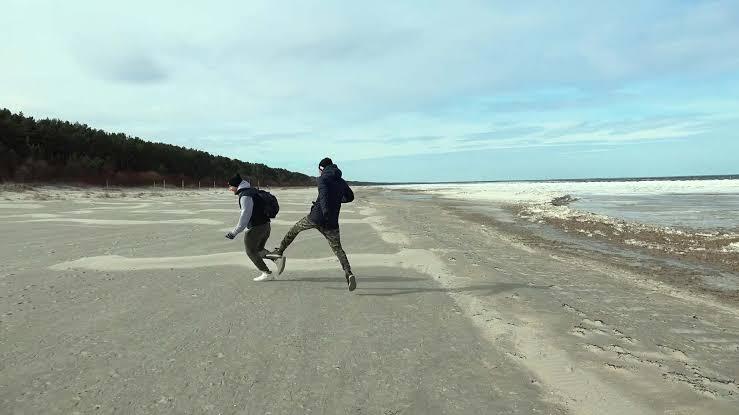 Cena do filme Bem-vindo à Chechênia em que dois homens, usando casaco e calça, se divertem em uma praia deserta.