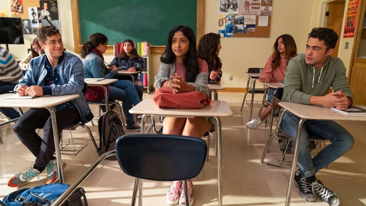 Cena da série Eu Nunca. À esquerda está Ben, ao centro Devi e à direita Paxton. Os três estão na sala de aula. Paxton e Ben estão olhando lateralmente, não dá para identificar se é para Devi ou se estão olhando um para o outro. Todos estão sentados com as pernas cruzadas e com carteiras de escola na cor creme à frente do corpo. Ben está usando uma blusa de botões azul escuro com pequenas bolinhas brancas. Usa uma jaqueta jeans por cima, calça preta e um tênis branco com a ponteira laranja e cinza e cadarços azuis. Devi está usando uma blusa gola careca no tom rosa queimado, uma blusa xadrez de frio por cima na cor cinza, um short que está encoberto pela blusa de frio e um tênis rosa. Ela usa uma pulseira na mão direita e seus cabelos estão soltos cobrindo o lado esquerdo do corpo. Suas mãos estão cruzadas em cima da mochila na cor coral que está em sua carteira. Paxton usa um casaco de moletom com capuz na cor verde musgo, calça jeans e um tênis all-star preto de cano alto. Ele está com as mãos em cima da carteira. Ao fundo, há seis estudantes sentados, duas delas conversando entre si, outros dois estão estudando e outros dois sem fazer nada. Ao centro e no fundo, há um quadro negro. À esquerda um mural com alguns pôsteres grudados, à direita outro mural com pôsteres e uma porta marrom claro.