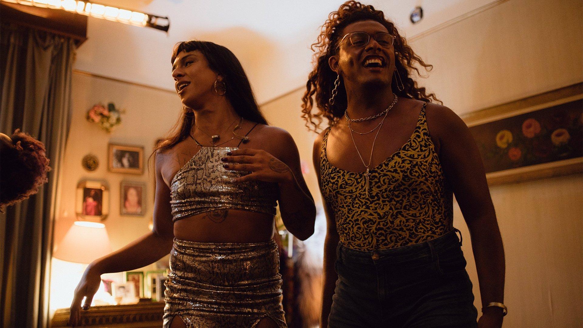 """Cena da série """"Manhãs de Setembro"""". Na imagem, a personagem Pedrita à esquerda usando um top e mini saia com estampas de tigre. Ao seu lado, Cassandra, de regata estampada e short. Ambas estão se movimentando e sorrindo. O cenário é um quarto."""