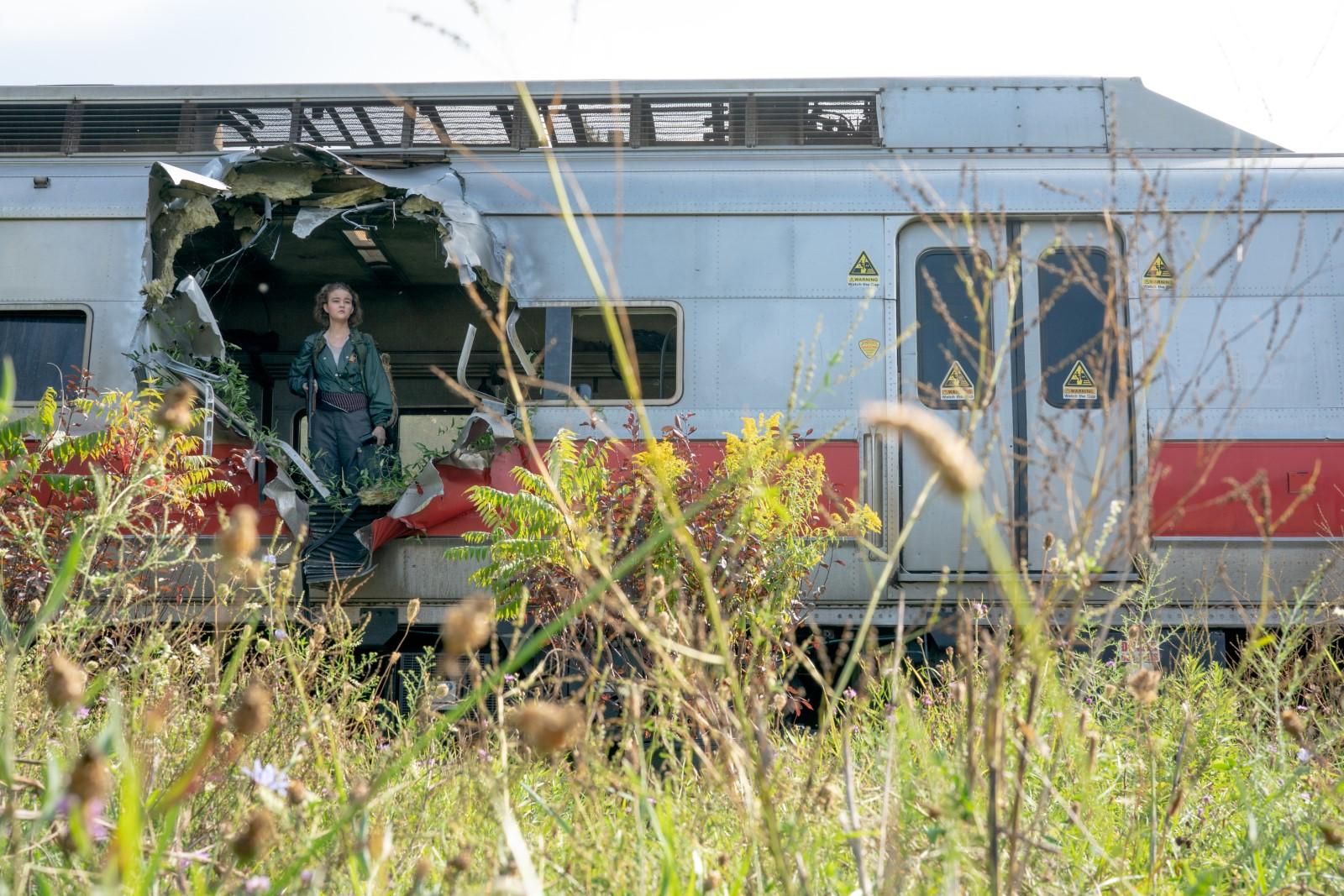 Cena do filme Um Lugar Silencioso - Parte II. A imagem é retangular. Na imagem há um trem cinza com uma linha horizontal em vermelho, na parte esquerda, o trem está com um buraco que leva a parte de dentro. Nesse buraco está Regan, que usa uma blusa verde e uma calça cinza, ela olha para frente. O chão onde está o trem tem mato alto.