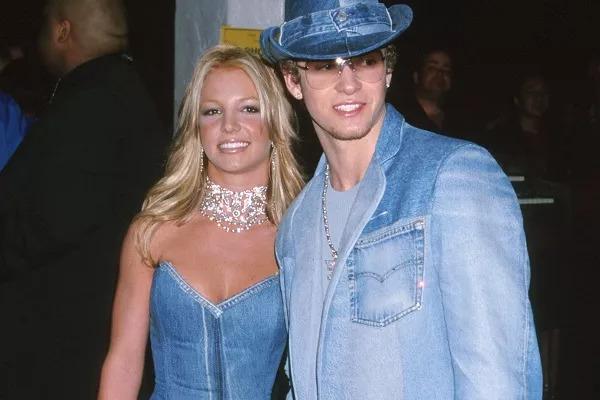 Foto de Britney Spears e Justin Timberlake. Ambos são brancos e loiros. O casal veste roupas jeans de cor azul claro. Ela usa o vestido acompanhado de um colar, e ele um terno junto de um chapéu.