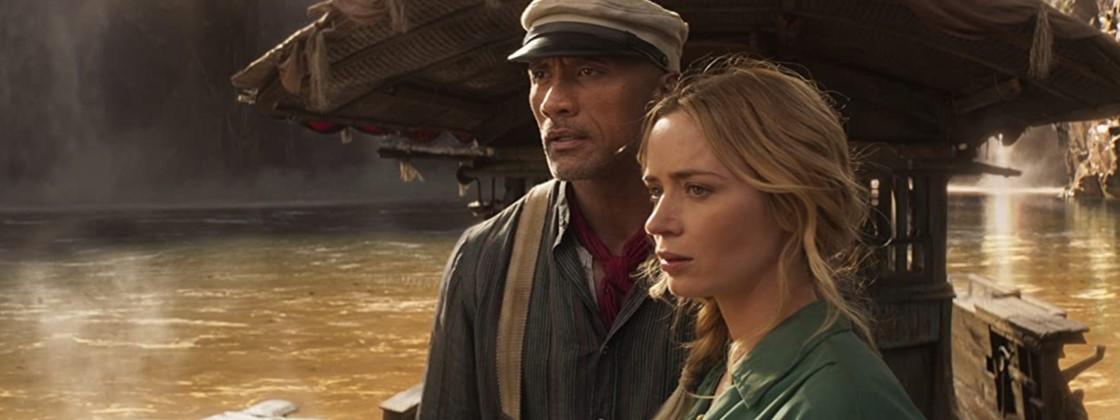 Cena do filme Jungle Cruise exibe uma mulher branca e um homem samoano em cima de um barco num rio. A mulher tem cabelo loiro longo e veste uma camisa verde. O homem usa uma boina e veste uma camisa cinza com suspensórios.