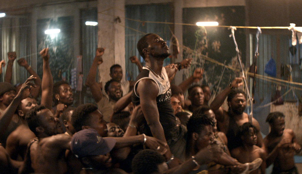A imagem retangular é uma cena do filme. Ao centro há um homem negro de cabelo preto e raspado, com um bigode e barbicha. Ele olha para cima e só pode ser visto da cintura para cima porque está sendo carregado por uma multidão. Ele usa uma camisa regata com detalhes pretos e brancos e também usa um relógio prateado. Ao redor há uma multidão de homens negros eletrizada com os braços para cima com os punhos fechados.