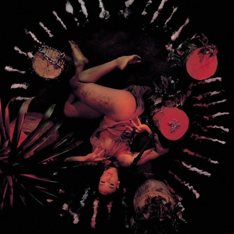 Capa do álbum Trava Línguas. Fotografia quadrada, com fundo preto. A cantora Linn da Quebrada ocupa o centro. Ela é uma mulher negra, de olhar sério, deitada de ponta cabeça, com pernas dobradas e à mostra. Ao redor dela, troncos de árvore, correntes, plantas e outros objetos formam um círculo. A cantora e os objetos são iluminados por uma luz avermelhada.