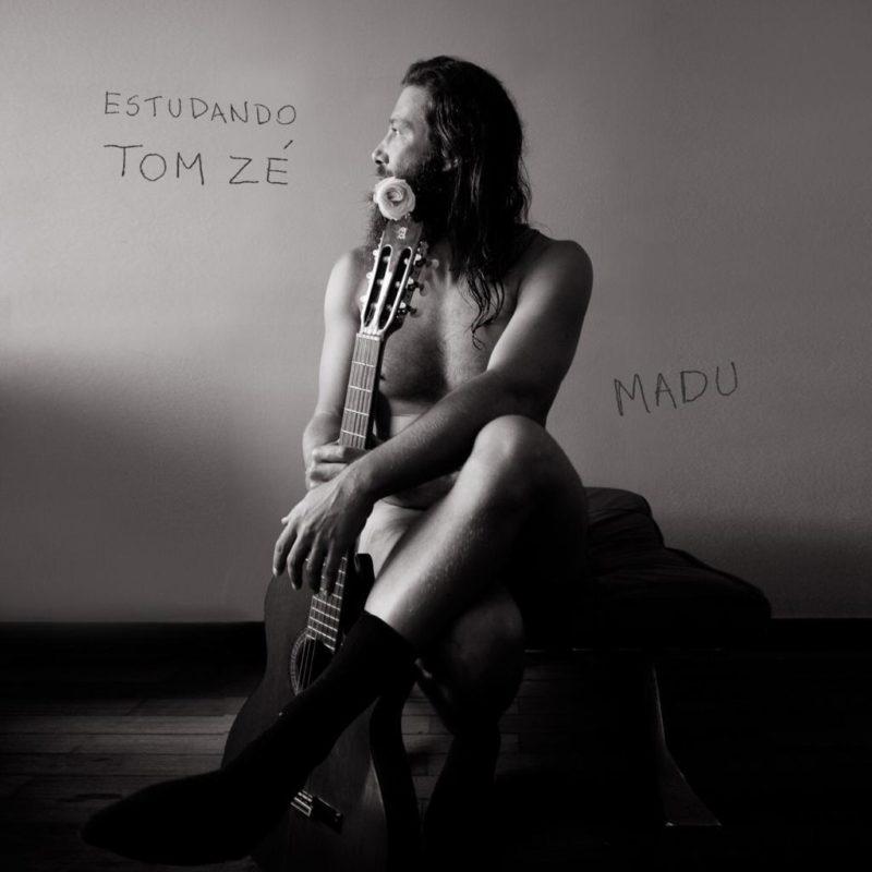 Capa do EP Estudando Tom Zé. Fotografia quadrada, em preto e branco. No canto superior esquerdo, lemos Estudando Tom Zé em letras pretas. O cantor Madu ocupa o meio da foto de cima a baixo. Ele é um homem branco, de cabelos compridos e barba, está de perfil, descamisado, sentado com as pernas cruzadas e segura um violão. Há uma rosa perto da boca de Madu. No lado direito, perto do centro da foto, lemos Madu em letras pretas.