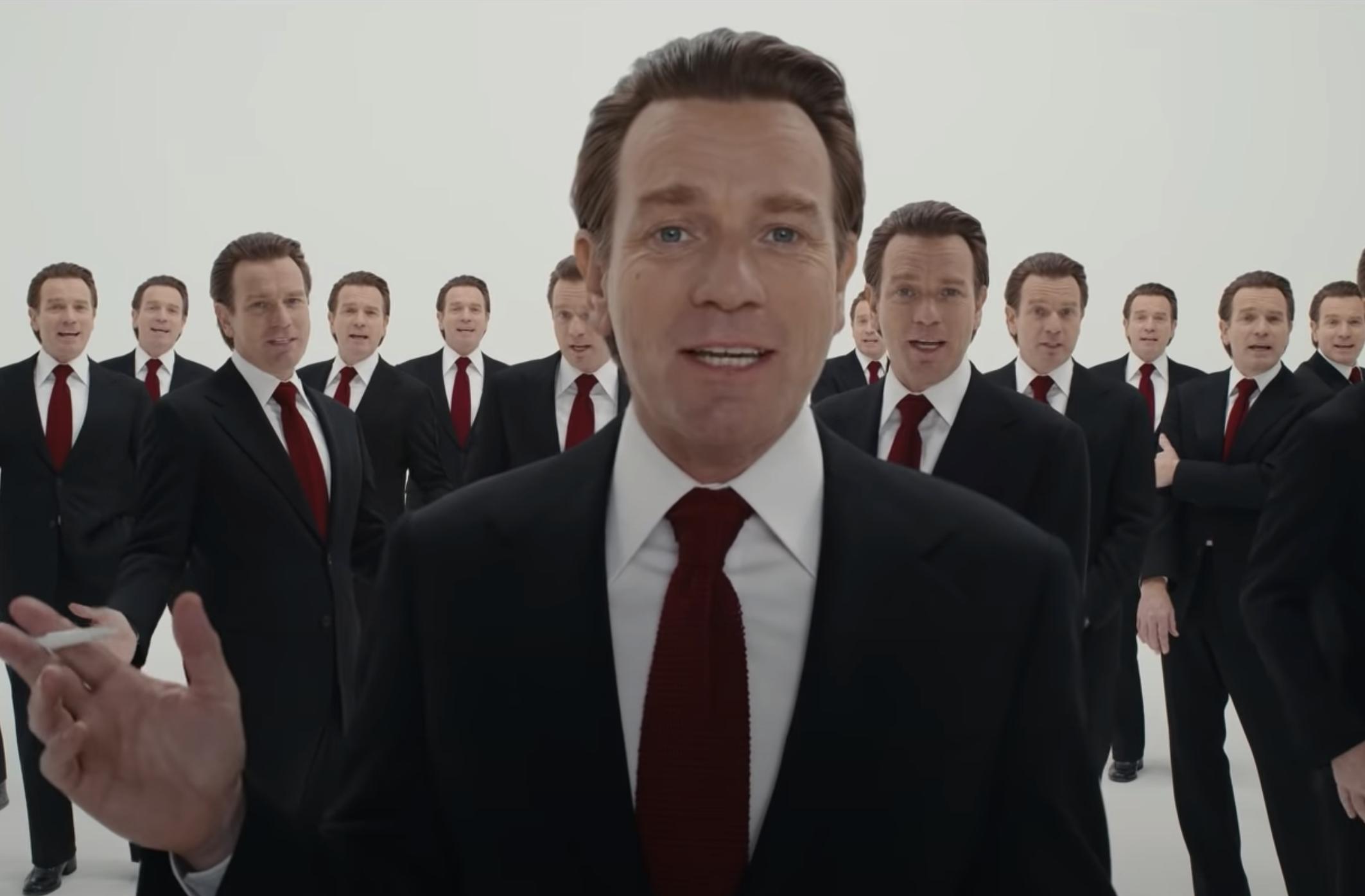 Cena da série Halston. Ewan McGregor, um homem branco, ruivo, de paletó e gravata vermelha está posicionado no centro, da cintura para cima. Atrás, também podemos ver várias reproduções de Ewan, todos usando a mesma roupa.