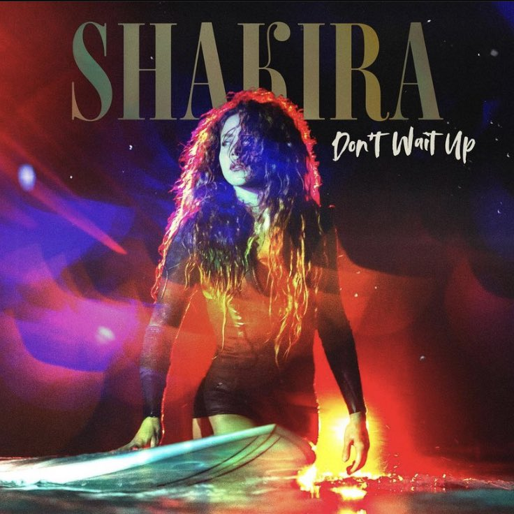 """Capa do single Don't Wait Up, de Shakira. A imagem é composta por um fundo escuro que imita efeitos de luzes roxas, vermelhas e amarelas. Sob este fundo, está uma fotografia de Shakira, uma mulher branca de cabelos frisados loiros. Ela está caminhando num mar que dá na altura de seus joelhos, olhando para o lado esquerdo. Shakira veste um macaquinho justo preto, que está molhado. Ao seu lado esquerdo, está uma prancha de surfe azul. Esse mar preenche parte da linha inferior da capa, e todo o resto é preenchido pelo fundo. No alto da imagem, ao centro, está escrito """"Shakira"""", bem grande e num tom de dourado, numa fonte serifada em caixa alta. Embaixo, num tamanho menor e posicionado à direita, está escrito o nome do single, numa fonte cursiva branca."""