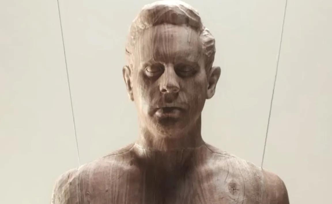 Imagem da série The Politician. Na figura há uma escultura de um busto de um homem, em madeira marrom clara. Sob um fundo branco, ainda há 2 correntes de aço segurando a escultura.
