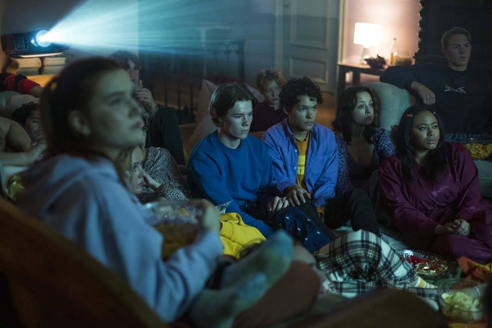 Cena da série Young Royals. A imagem mostra um grupo de adolescentes assistindo filme numa sala grande. A imagem é capturada meio de lado, num panorama do lado direito, e o foco está num casal do jovens ao centro do grupo. Eles estão sentados no chão, ao redor de outros adolescentes, e são interpretados por Edvin Ryding e Omar Rudberg. Primeiro, do lado esquerdo, está Wilhelm, a personagem de Edvin, um adolescente branco de cabelos médios lisos e loiros. Ele veste um moletom azul escuro e está entrelaçando os dedos com as mãos de Simon, personagem de Omar. Simon é um adolescente negro de pele clara, de cabelos ondulados castanhos. Ele veste uma camisa jeans em cima de uma blusa amarela mostarda e suas mãos estão em cima do joelho de Wilhelm. Os dois olham para a frente, e atrás deles existe um aparelho que projeta uma luz na frente deles. Ao redor, existem outros adolescentes sentados nos sofás e no chão, ao centro, assim como os dois, e também vasilhas com pipocas e doces.