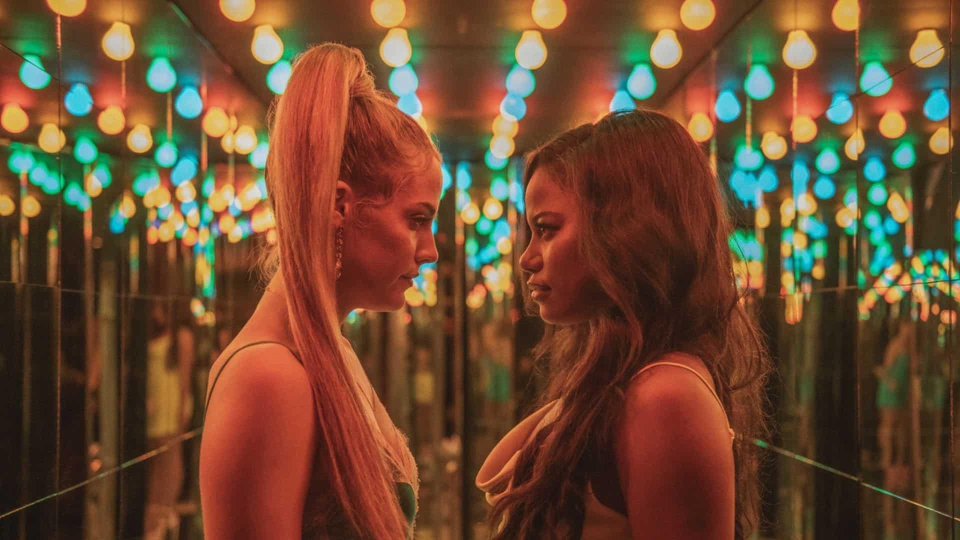 Cena do filme Zola mostra uma mulher negra e uma mulher branca se encarando em um ambiente com paredes espelhadas e várias lâmpadas azuis e amarelas no teto. A mulher branca tem cabelo loiro, longo e preso num rabo de cavalo. A mulher negra tem cabelo castanho volumoso.