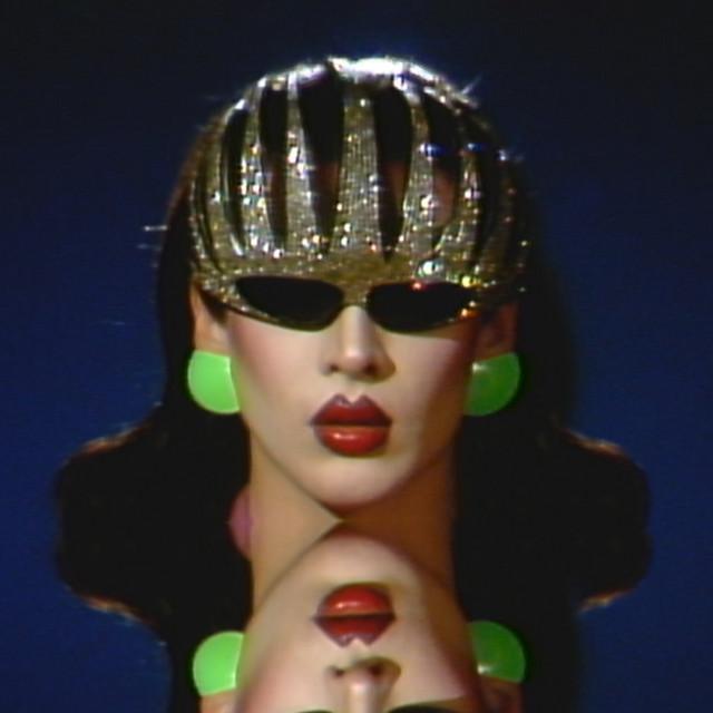 Capa da música Mistress Violet, de Allie X e Violet Chachki. A foto mostra Violet, uma drag queen branca e de cabelos pretos, óculos escuros, coroa prateada e brincos verdes, olhando para frente, com o reflexo do espelho abaixo dela.