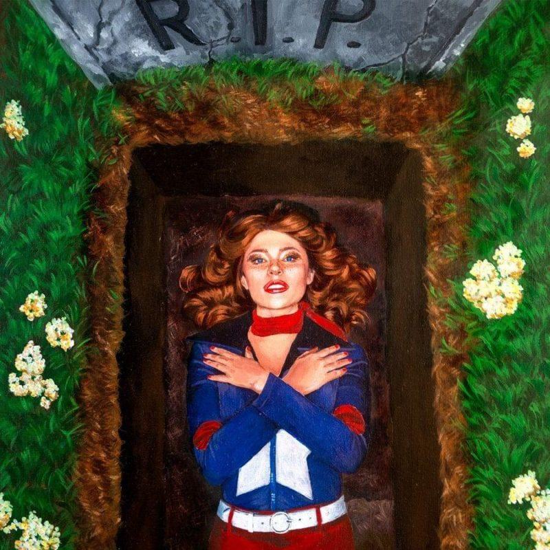 Capa de Faking My Own Death. Nela está o desenho de uma mulher branca de cabelo ruivo espalhado pelo chão. Ela usa um uniforme de super herói azul e vermelho, olhando para cima com as mãos cruzadas na frente do corpo. A mulher está deitada dentro de uma cova. Ao seu redor estão algumas flores brancas plantadas em um gramado e uma lápide escrito R.I.P.