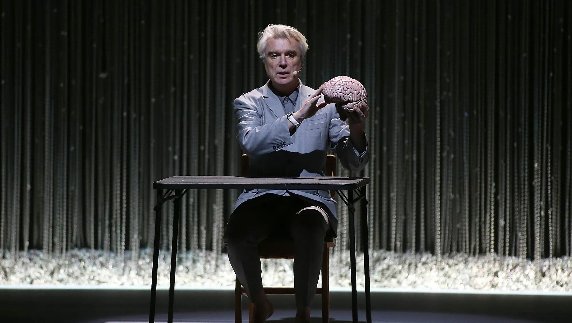 Cena do especial David Byrne's American Utopia. A imagem mostra David Byrne, um homem branco de meia-idade, sentado à uma carteira escolar e segurando um modelo de um cérebro de plástico. Ele o estende à sua frente segurando-o com sua mão esquerda, enquanto aponta para ele com a mão esquerda apoiada. Ao fundo desfocada, há uma cortina feita de correntes finas prateadas.