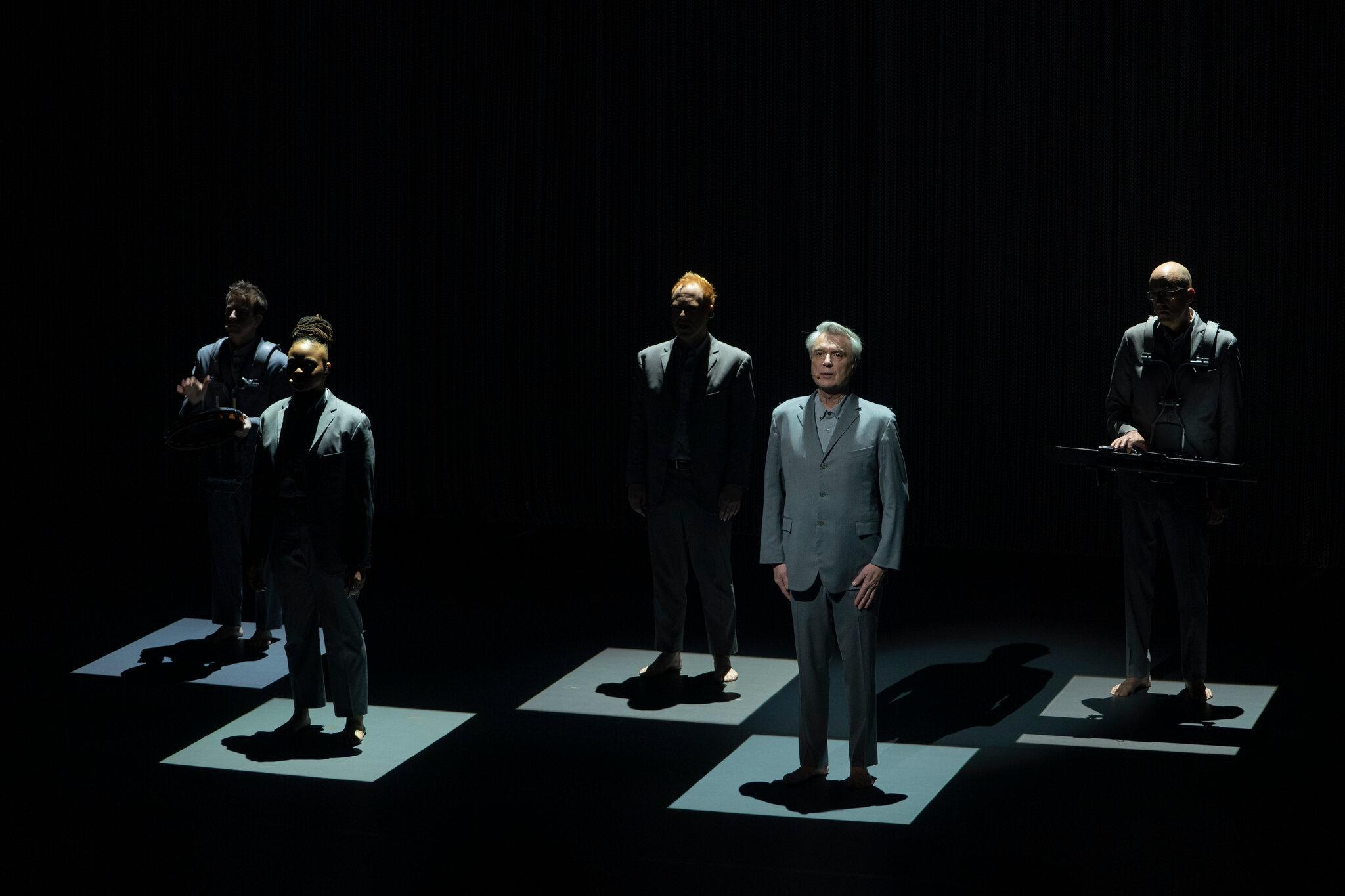 Cena do especial David Byrne's American Utopia. Cinco pessoas vestindo ternos cinzas e descalços se encontram em pé, voltados para a mesma direção. A ambientação se encontra toda escura, com exceção de cinco quadrados iluminados posicionados logo abaixo das pessoas. Da esquerda para a direita são vistos um homem branco tocando um tambor, uma mulher jovem e negra, um jovem branco e ruivo, e um homem branco de meia idade, os três com os braços paralelos ao corpo, e por fim um homem branco calvo tocando um teclado suspenso em seu próprio corpo. Todos têm sua fisionomia ofuscada pela ausência de luz frontal, com exceção do homem de meia idade, que é David Byrne, que recebe uma luz frontal criando uma sombra atrás de si para além do quadrado.