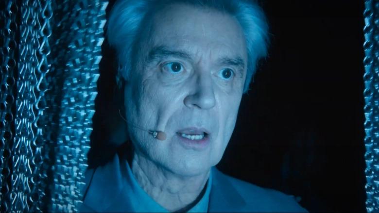 Cena do especial David Byrne's American Utopia. A imagem mostra de perto um homem branco de meia-idade, David Byrne, vestindo um terno cinza e cantando com um microfone na lateral de seu rosto. Em seus dois lados, há bem próxima uma cortina formada por correntes prateadas finas.