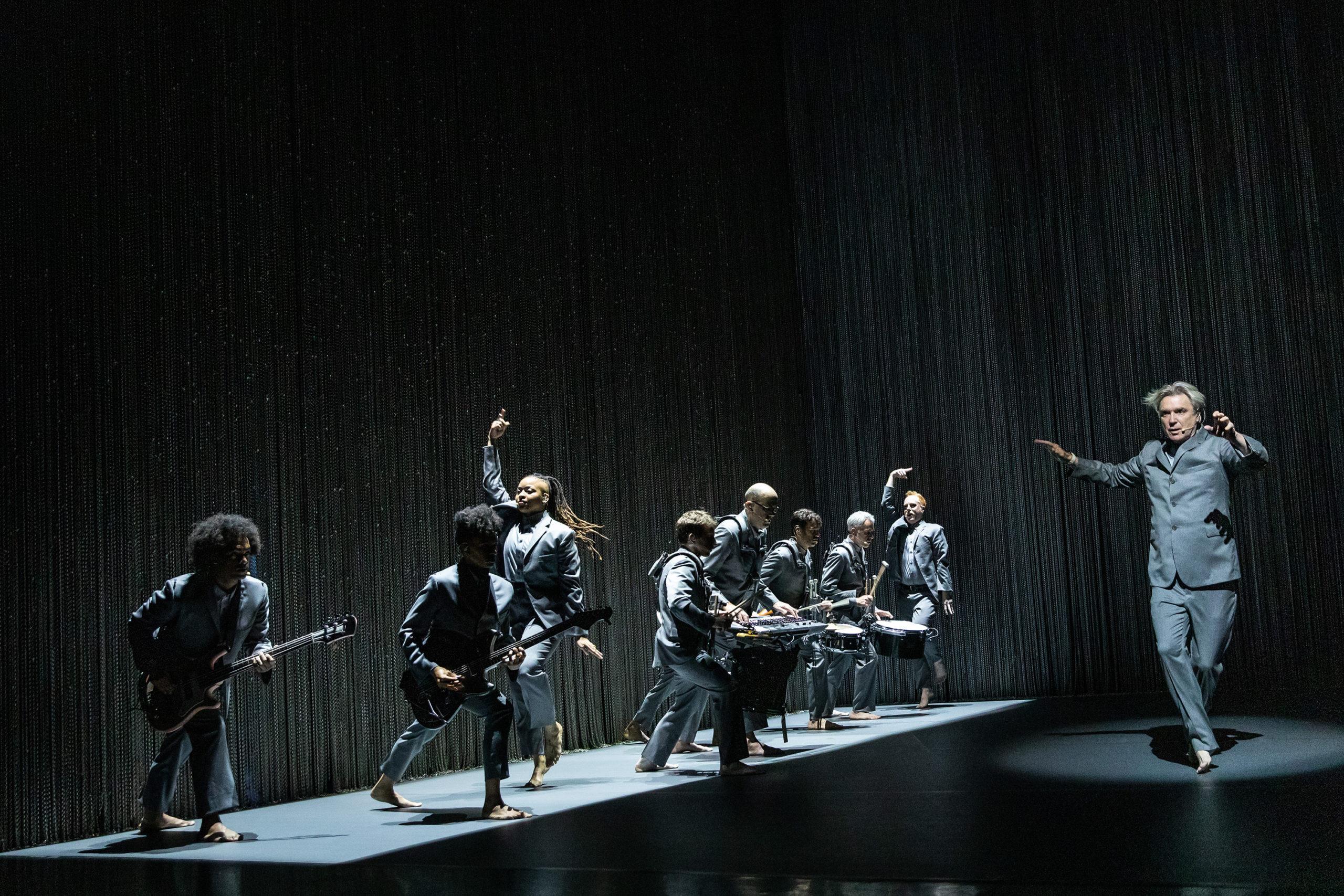 Cena do especial David Byrne's American Utopia. A imagem mostra parte do elenco do musical no palco enfileirada à esquerda, todos de terno cinza e descalços, com os instrumentistas voltados para o centro do palco onde David Byrne, um homem branco de meia-idade, faz um passo de dança com as pernas torcidas e os braços suspensos no ar. Da frente para trás à esquerda, são vistos um homem e uma mulher negros tocando respectivamente baixo e guitarra, uma mulher negra com cabelo preso cheio de tranças executando um passo de dança com um braço estendido para cima, quatro instrumentistas, e ao fundo um homem branco e ruivo executando o mesmo passo que a mulher negra. O palco é cercado por uma alta cortina formada por correntes prateadas finas.