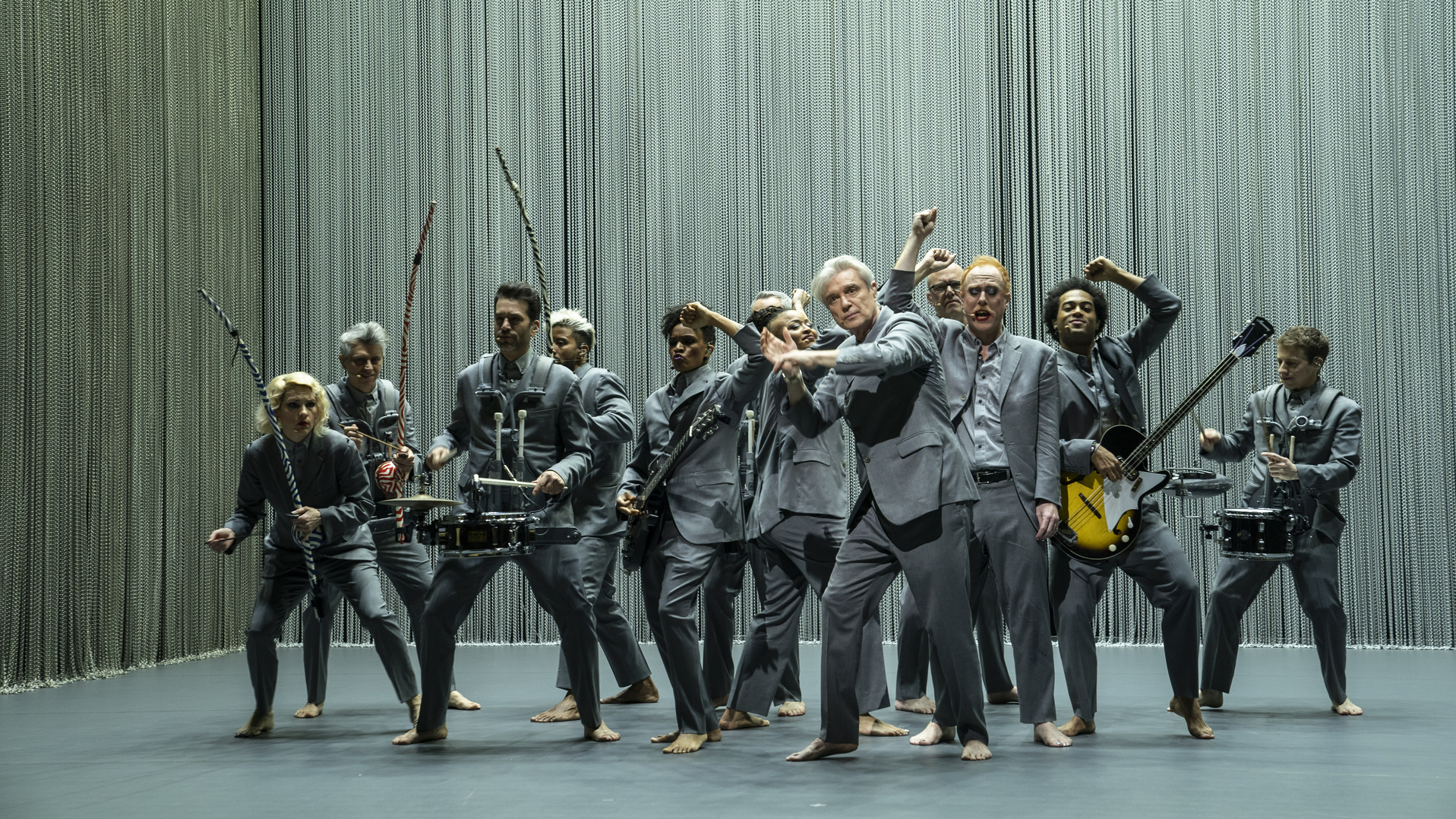Cena do especial David Byrne's American Utopia. A imagem mostra o elenco aglomerado no palco, doze pessoas vestindo ternos cinzentos e descalços, grande parte deles tocando diferentes instrumentos. Há três berimbaus à esquerda, além de guitarra, baixo, e instrumentos percussivos. Ao centro e à frente, David Byrne, um homem branco de meia-idade, faz um gesto de dança com os braços. Atrás deles, algumas das pessoas levantam os braços com os punhos fechados. O palco é cercado por uma alta cortina formada por correntes prateadas finas.