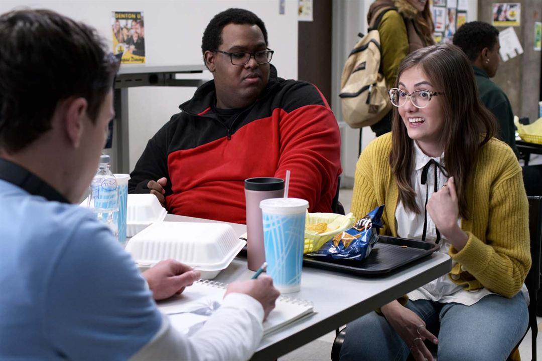 Cena da série Atypical. Imagem estática. Os três personagens estão em um refeitório na faculdade. No canto esquerdo vemos Keir Gilchrist que interpreta o protagonista Sam de costas. Ele é um homem branco de cabelo castanho curto e liso. Utiliza uma camiseta azul por cima de uma blusa manga longa branca. Está sentado de frente com outras duas pessoas. Em frente a Sam está Sid, interpretada por Tal Anderson. É uma mulher branca de cabelo castanho longo e liso. Ela veste uma camisa branca de laço preto na gola e por cima um cardigan amarelo, juntamente de calça jeans azul médio. Está sentada. Ao lado de Sid está Jasper, personagem de Domonique Brown. É um homem negro, de cabelo preto, crespo e curto. Ele utiliza um moletom vermelho e preto e está olhando para Sid. Também está sentado.