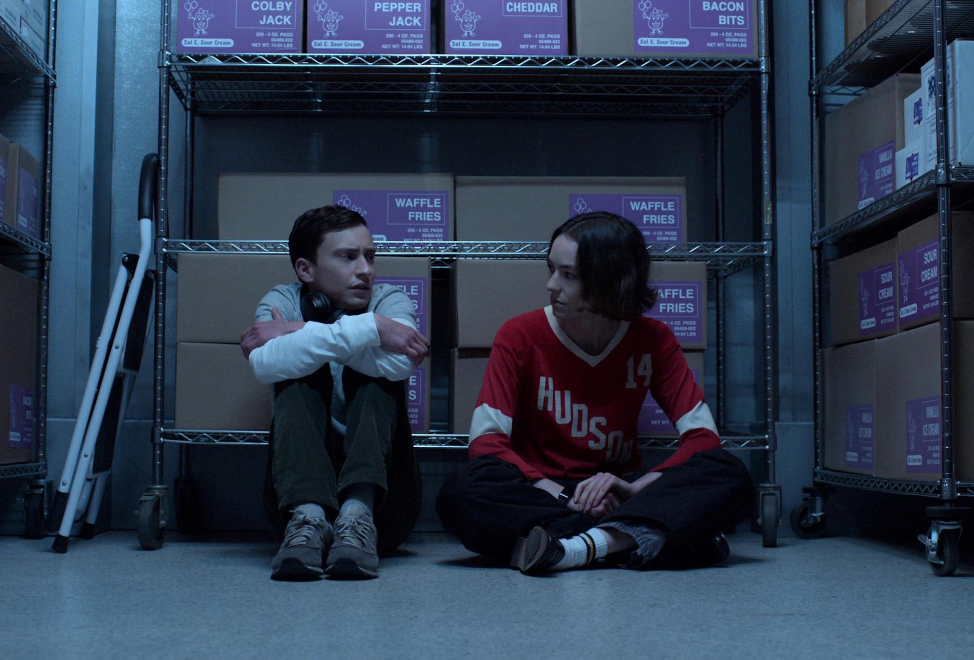 """Cena da quarta temporada de Atypical. Sam (Keir Gilchrist) e Casey (Brigette Lundy-Paine) estão sentados no chão de um depósito, sentados de costas para uma estante com caixas de papelão. À esquerda, Sam, caucasiano, cabelos pretos e curtos, usando uma calça esverdeada e uma blusa clara, abraçando os joelhos e olhando nervoso para sua irmã. Casey, caucasiana e cabelos castanhos quase até os ombros, está sentada de pernas cruzadas, usando uma calça jeans e uma camiseta de mangas longas vermelha e branca com a palavra """"Hudson"""" escrita verticalmente e o número 14 no ombro direito, olhando preocupada para Sam. O local está iluminado por uma luz azul fria."""