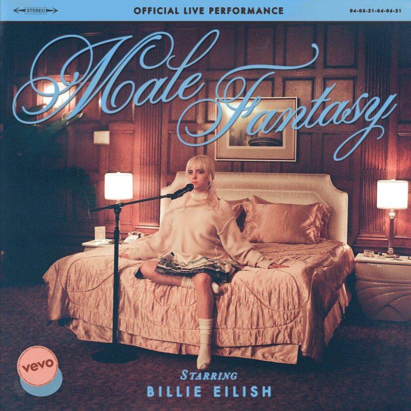 """Capa da performance de Male Fantasy. Billie Eilish, mulher branca e loira, veste uma saia azul e moletom branco, com uma meia também branca no pé. Ela está sentada em uma cama de casal bege com travesseiros rosas e uma parede de madeira atrás. Na frente da cantora está um microfone segurado na sua altura por um pedestal. No canto superior da imagem está uma faixa azul onde dentro está o texto """"OFFICIAL LIVE PERFORMANCE"""" em preto, seguido por """"Male Fantasy"""" escrito em letra cursiva azul. No canto inferior está, também em azul, """"starring Billie Eilish"""", com o símbolo da Vevo a sua esquerda."""