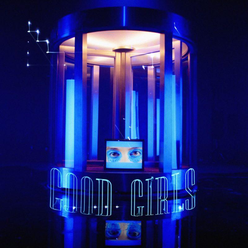 Capa do single Good Girls, da banda CHVRCHES). Uma porta giratória azul circular com um monitor apoiado na frente, exibindo os olhos pintados de azul em um rosto branco. O título da faixa, Good Girls, aparece ao pé da porta, em letras finas e azuis. A porta é iluminada por uma luz branca na parte de dentro, enquanto o lado de fora está banhado em azul escuro.