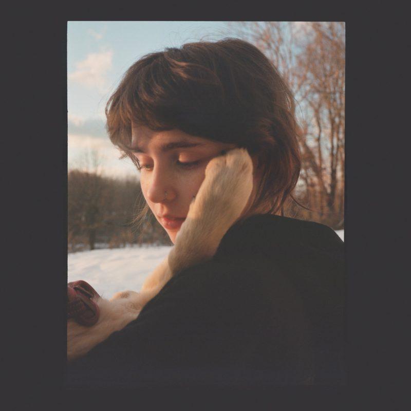 Capa do álbum Sling, da cantora Clairo. Emoldurada por um quadrado preto desbotado, uma foto de Clairo, usando uma blusa preta, olhando para sua cadela, Joanie, que tem uma das patas de pelos brancos levantadas tocando em seu rosto. Clairo é caucasiana e possui cabelos castanhos que vão até as orelhas. Atrás dela, um dia claro em uma paisagem de árvores sem folhas, com o chão coberto de neve.