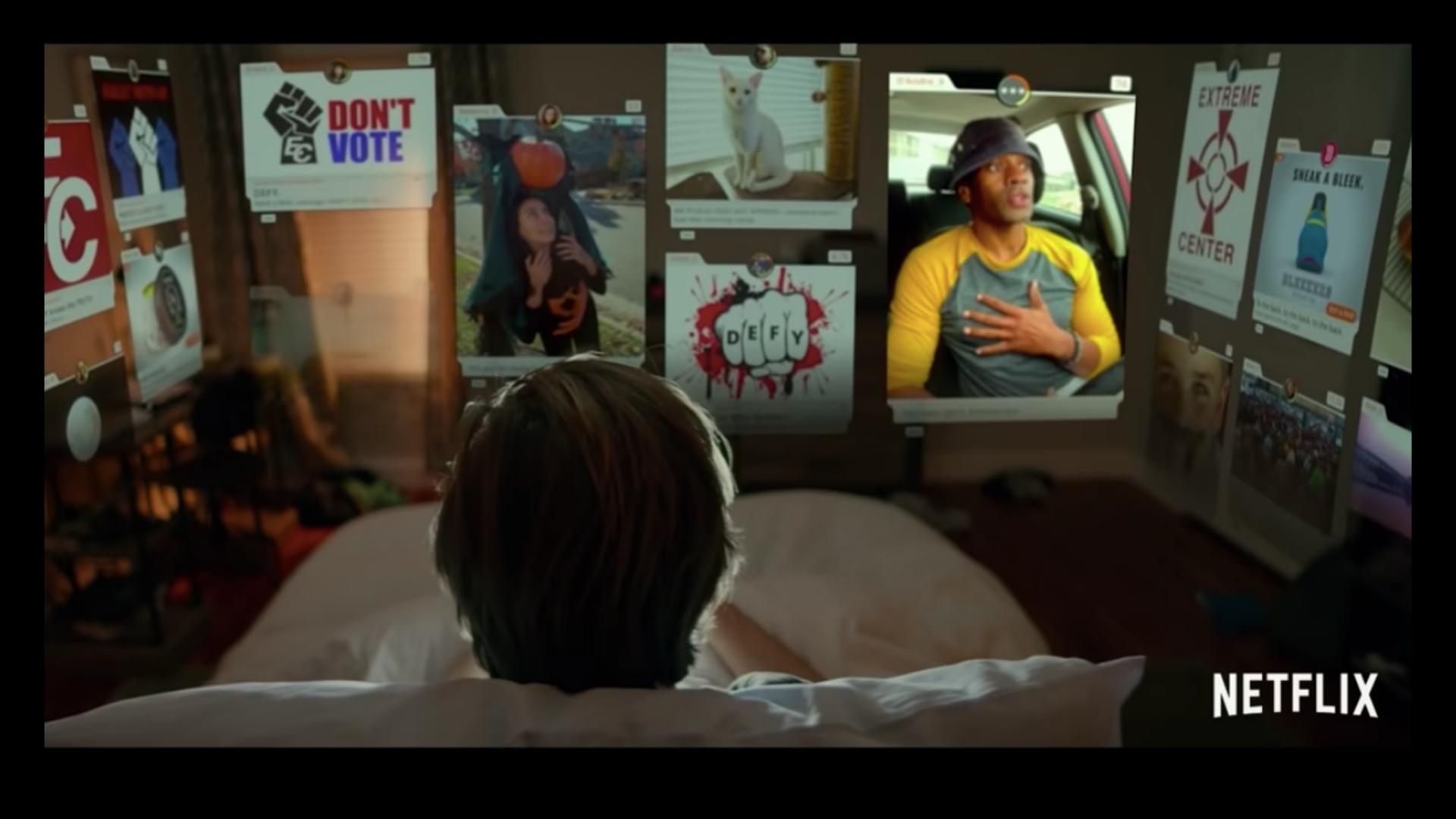 Cena do filme O Dilema das Redes. A imagem mostra por trás um adolescente loiro sentado em uma cama. Vemos apenas sua cabeça apoiada no travesseiro. À sua frente, alinhados às paredes do quarto, estão diversas imagens suspensas no ar, simulando abas de navegadores de internet.