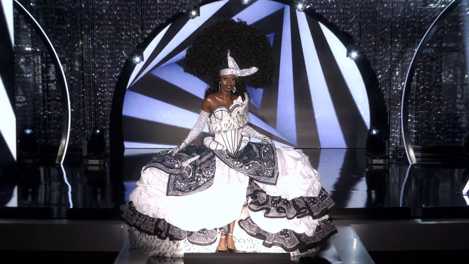 A imagem mostra Symone, uma participante da 13ª temporada de RuPaul's Drag Race. Ela é uma drag queen negra, e está vestindo uma grande peruca crespa em formato de meio círculo. Ela usa uma faixa branca na cabeça que sobe para a peruca. Seu vestido é branco e preto, com diversas estampas e babados.