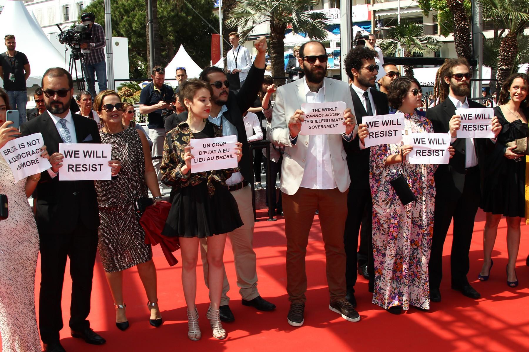 Foto do elenco de Aquarius no Festival de Cannes. São dez pessoas, entre homens e mulheres de pele clara que, em fila indiana, sob o tapete vermelho, seguram cartazes em inglês e francês com mensagens de protesto contra o impeachment da ex presidenta Dilma Rousseff. Todos estão usando roupas formais - os homens de terno e as mulheres de vestido. A foto foi tirada de dia.