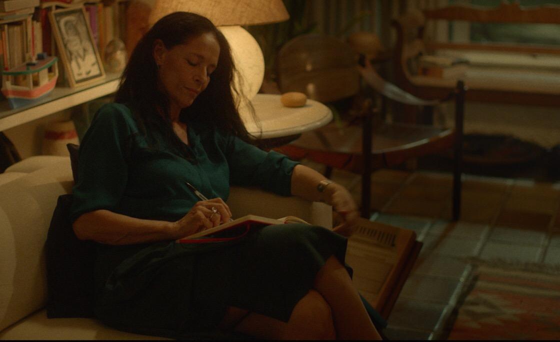 Cena do filme Aquarius. Clara, personagem de Sônia Braga, está sentada com as pernas cruzadas no sofá de sua sala, escrevendo em um caderno que apoia sob o colo. Dessa vez, Clara está com os cabelos soltos e usa um vestido verde. Atrás dela, temos uma estante de livros e uma mesa de canto, com um abajur ligado. Existem outros objetos ao fundo, mas estão desfocados. A cena provavelmente foi gravada à noite. A única luz que existe é a que vem do abajur, dando um ar aconchegante à sala.