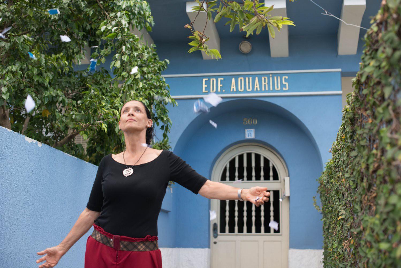"""Sônia Braga em frente ao edifício Aquarius, cenário do filme que leva o mesmo nome. Ela está de braços abertos, olhando para cima, e usa uma blusa preta de mangas até o cotovelo. Novamente, ela aparece entre os dois muros - o jardim vertical e o de concreto. Atrás, podemos observar a fachada do edifício, azul celeste, com os dizeres """"Edf. Aquarius"""" e """"560"""". A entrada e a porta têm formatos arredondados."""