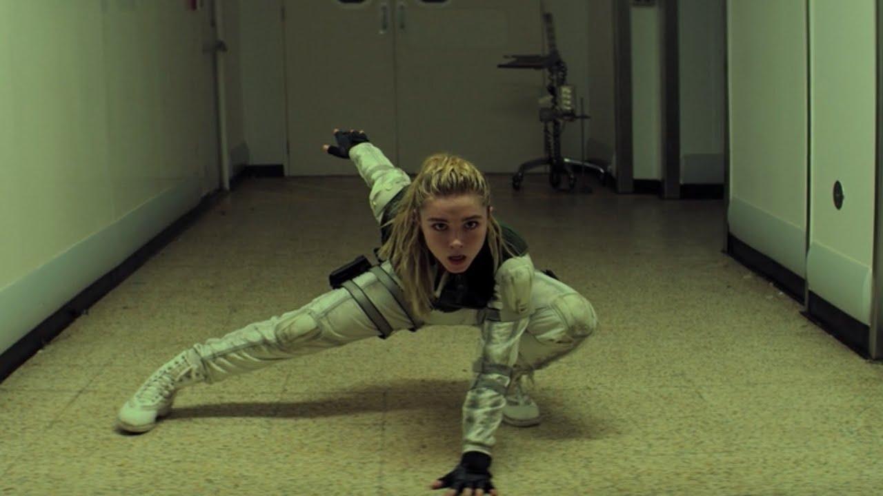 Cena do filme Viúva Negra. Ao centro, em um corredor vazio, Yelena, uma mulher branca, de cabelos loiros longos presos em um rabo de cavalo, vestindo um uniforme branco, um colete verde escuro e luvas pretas, está agachada no chão em uma pose de combate.