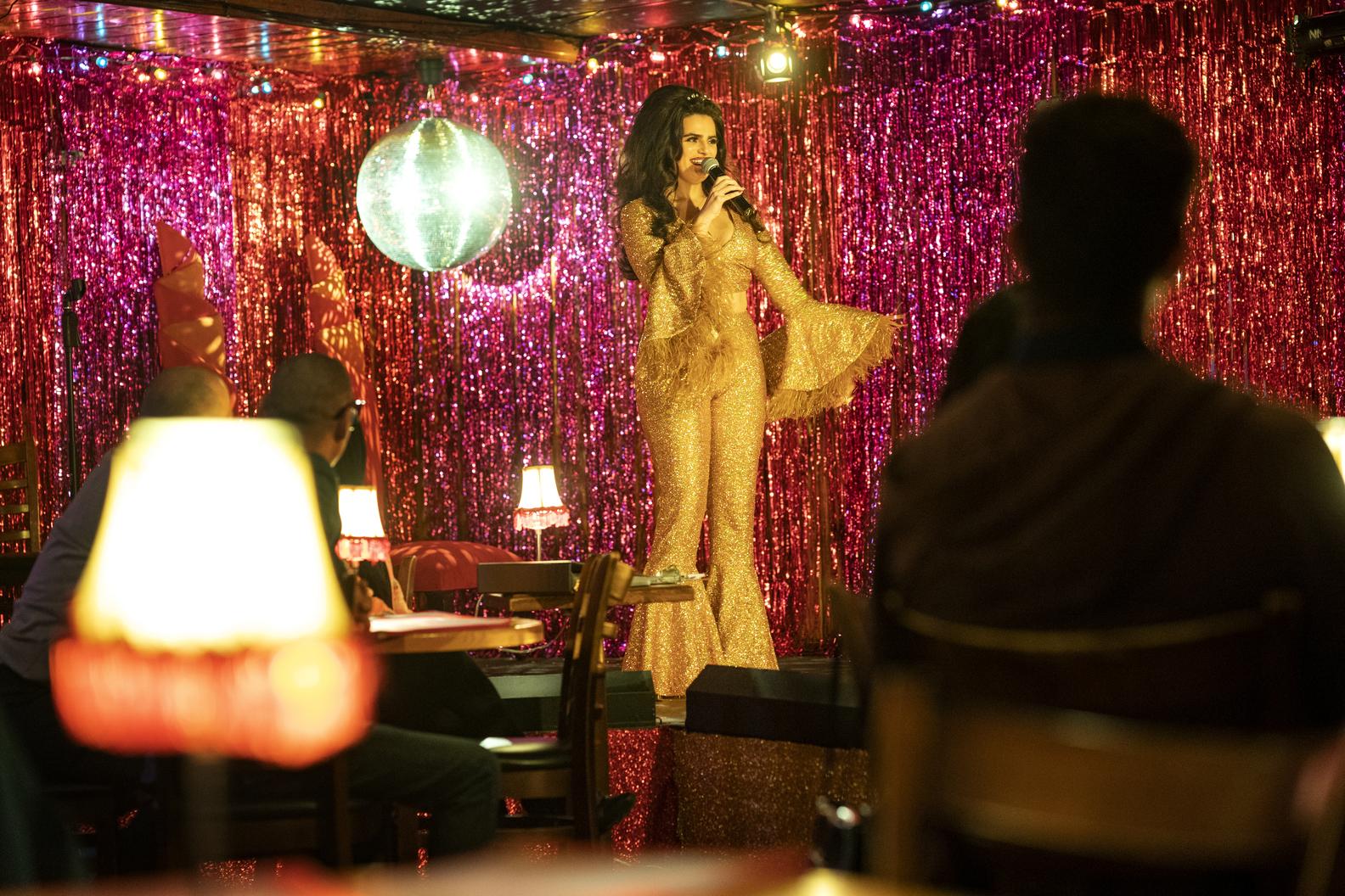 Cena da série Generation. A cena mostra Ana, uma mulher latina, usando macacão dourado, em cima de um palco, falando no microfone e com um fundo de papéis rosas atrás dela.